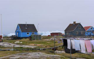 bunte Häuser mit Wäscheleine vor Eisberg