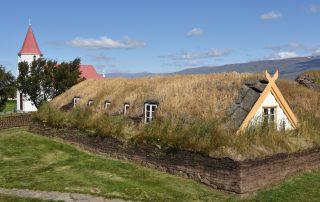 Grasbewachsenes Haus auf Island mit Kirche im Hintergrund