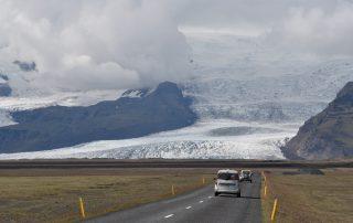 Isländische Straße mit Gletscher im Hintergrund