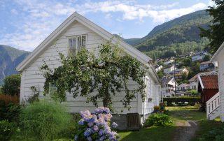 Weißes Holzhaus im Fjordland mit Fliederblüte