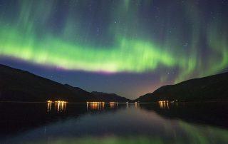 Nordlichtspiegelung im Fjord