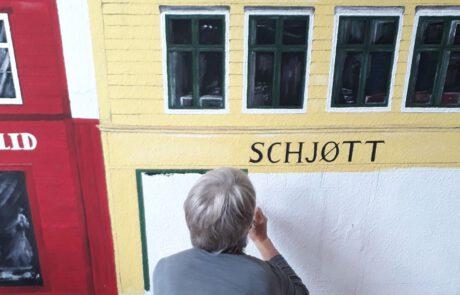Die Künstlerin an der Wand
